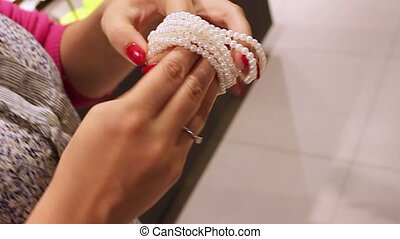 Young blonde woman in shop trying bracelet jewelry