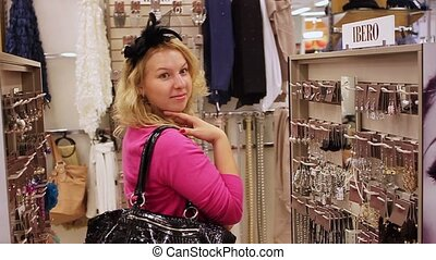 Young blonde woman in shop watching hair accessories