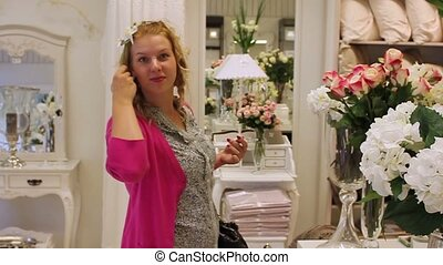 Young blonde woman in shop watching flowers