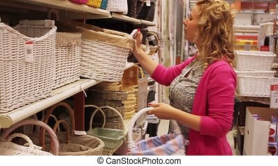 Young blonde woman in shop watching baskets