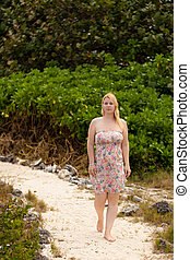 Young blonde woman in summer dress walking barefoot