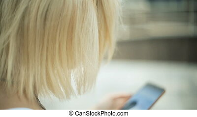 Young blonde woman in the park, uses a smartphone, internet, text, looks around quietly Back view
