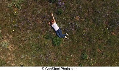 Young blonde woman lies in a field