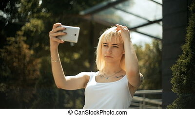 Young blonde woman looks at reflection on a smartphone straightens her hair uses the phone as mirror
