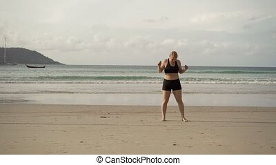 Young blonde woman making sport exercises on a beach