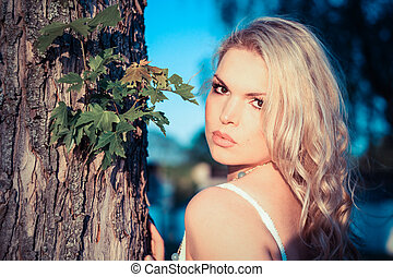 Young Blonde Woman next to a tree