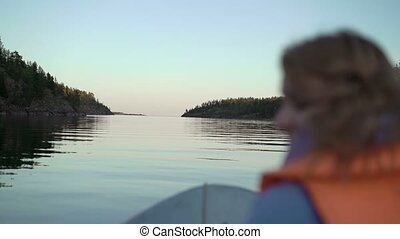 Young blonde woman on a boat in life jacket at the evening