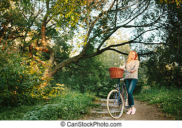 Young blonde woman on a vintage bicycle