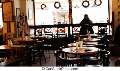 Young blonde woman on black coat having a cup of coffee  in empty old-style fashionable restaurant