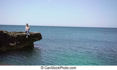 Young blonde woman on rocks near sea