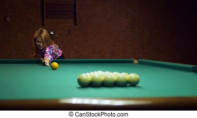 Young blonde woman plays in russian billiards.