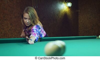 Young blonde woman plays in russian billiards. Woman hits...