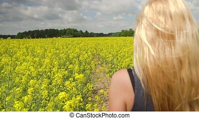 young blonde woman posing in beautiful rapeseed field - ...