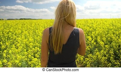 young blonde woman posing in beautiful rapeseed field -...