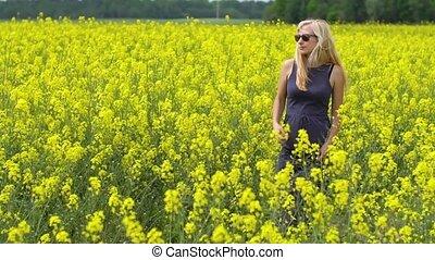 young blonde woman posing in beautiful rapeseed field -...