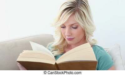 Young blonde woman reading a book