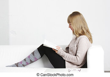 Young blonde woman reading book sideview
