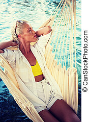 blonde woman resting on hammock