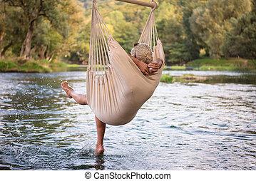 blonde woman resting on hammock