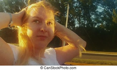 Young blonde woman riding in a convertible car