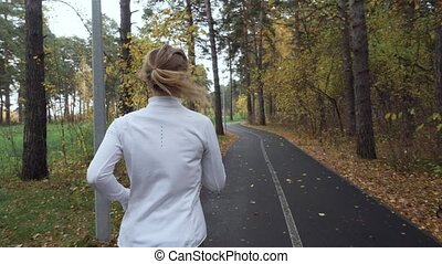 Young blonde woman running in the autumn park.