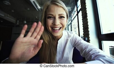 Young blonde woman showing hello gesture to somebody talking by internet, close-up