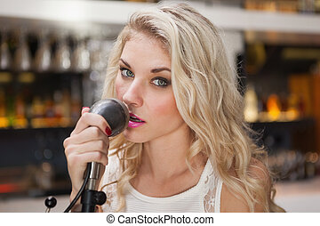 Young blonde woman singing while looking at camera at the...