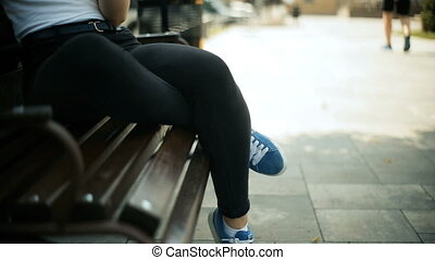Young blonde woman sits on a bench in the park uses a smartphone internet text looks around quietly
