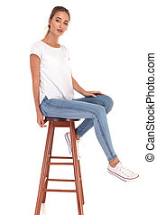 young blonde woman sitting on a stool