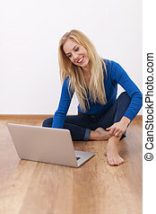 Young blonde woman sitting on floor with laptop