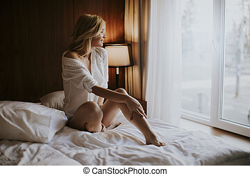 Young blonde woman sitting on the bed in the room looks melancholy