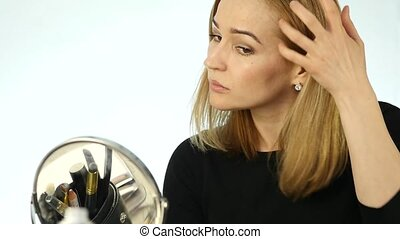 Young blonde woman standing in front of the mirror at home and correcting her hair
