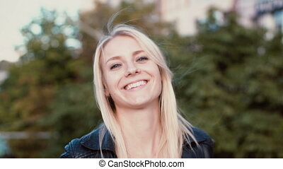 Young blonde woman standing in the park and looking at camera. Girl seriously looks and then starts to smile, laugh.
