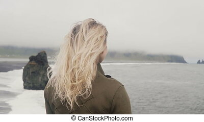 Young blonde woman standing on the black beach in iceland,...