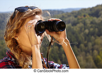 Young blonde woman tourist   on a cliff looking through binoculars on the autumn landscape