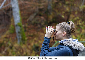 Young blonde woman tourist on a cliff looking through binoculars on the autumn landscape.