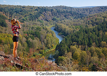 Young blonde woman tourist   on a cliff looking through binoculars on the autumn landscape with the river Berd