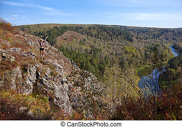 Young blonde woman tourist on a cliff over the river Berd