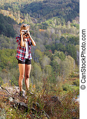 Young blonde woman tourist on a cliff taking pictures of the autumn landscape on old film camera