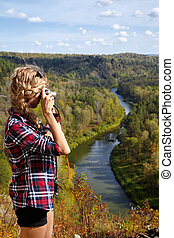 Young blonde woman tourist on a cliff taking pictures of the autumn landscape with the river Berd on old film camera