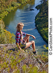 Young blonde woman tourist sit on a cliff on background of siberian autumn landscape with the river Berd