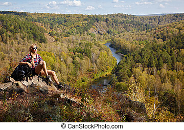 Young blonde woman tourist with backpack sitting on a cliff on background of siberian autumn landscape with the river Berd