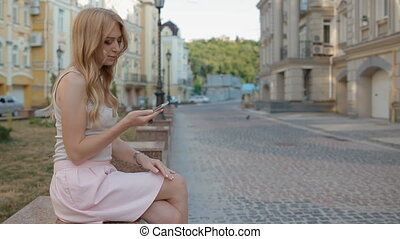 Young blonde woman use her phone outdoor
