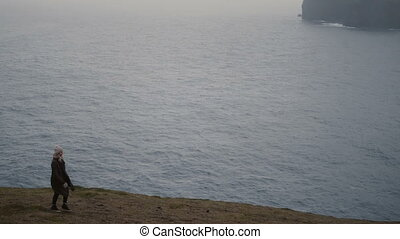 Young blonde woman walking on the shore of the sea in foggy...