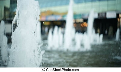Young blonde woman walks in the city passes near the fountain, wets her hands, touches the water.
