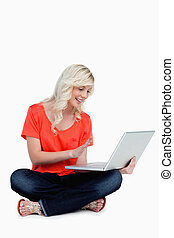 Young blonde woman waving her hand in front of her laptop
