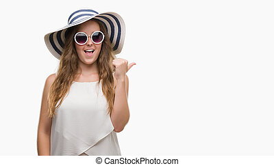 Young blonde woman wearing sunglasses and summer hat pointing and showing with thumb up to the side with happy face smiling