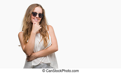 Young blonde woman wearing sunglasses looking confident at the camera with smile with crossed arms and hand raised on chin. Thinking positive.