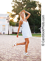 Young blonde woman wearing white dress and hat posing outdoors