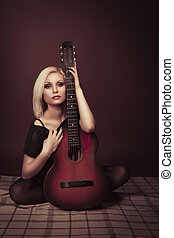 Young blonde woman with a guitar